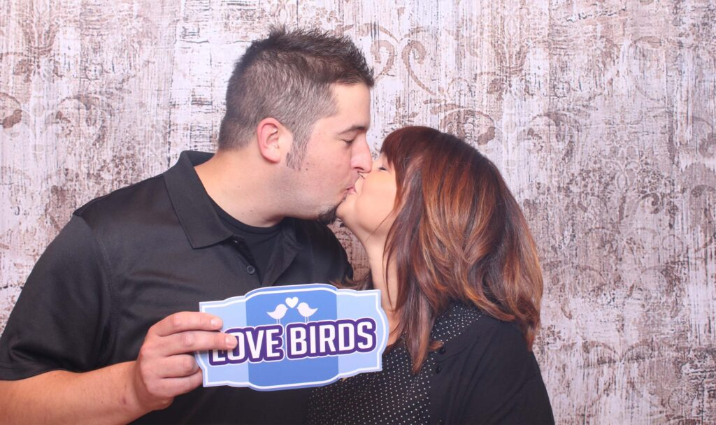 """Couple with """"love birds"""" sign"""